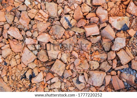A pile of old broken red clay brick rubble after demolition of an old building lies on the ground on a building site Royalty-Free Stock Photo #1777220252