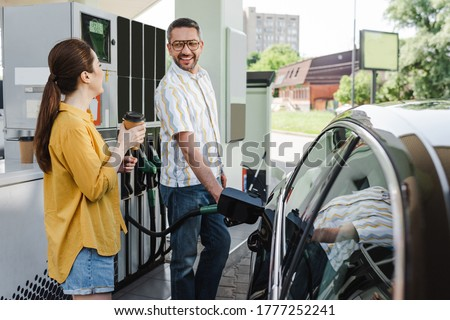 Selective focus of smiling man looking at wife with coffee to go while refueling car on gas station Royalty-Free Stock Photo #1777252241