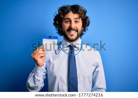 Young handsome business man with beard holding id card identification over blue background with a happy face standing and smiling with a confident smile showing teeth