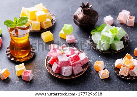 Assortment of Turkish delights on a copper tray with glass of tea. Grey background. Royalty-Free Stock Photo #1777296518