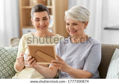 family, generation and people concept - happy smiling adult daughter and senior mother looking at photo at home
