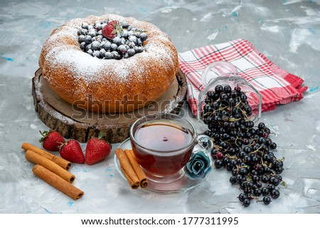 a front view fruit cake with fresh blueberries and along with cup of tea on the bright desk cake biscuit sweet sugar #1777311995