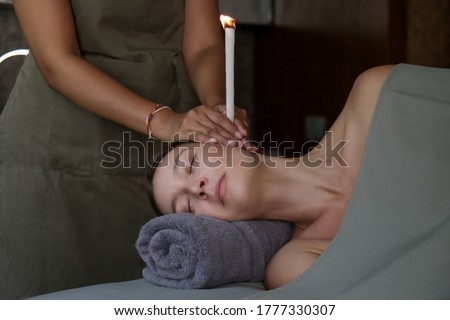 Woman receiving ear candle treatment at spa. Ear coning or thermal-auricular therapy. Royalty-Free Stock Photo #1777330307