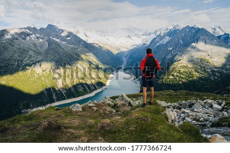 Adventurous man on the edge of a cliff overlooking the beautiful Austria Alps and Lake during a vibrant summer sunset. Taken in Hiking to the Olperer Hut in the Zillertal Alps in Austria  Royalty-Free Stock Photo #1777366724
