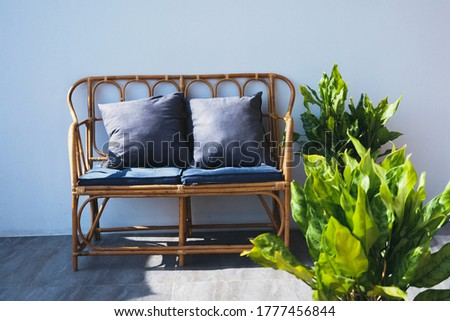 Modern loft living room with plywood wall and wooden floor, blue retro sofa with pillows and green tropical plants near low sill window.  interior jungle style #1777456844