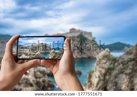 Tourist taking photo of stunning view of Dubrovnik city wall. Man holding phone and taking picture of fortress walls, rocky coast and blue sea in Dubrovnik, Croatia.