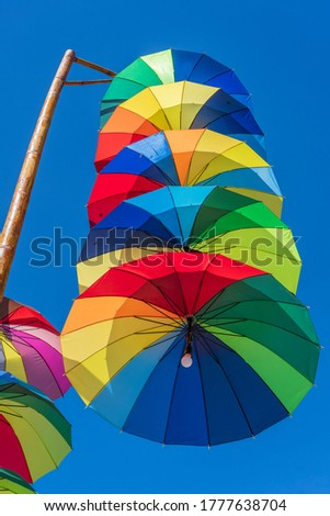 Street lamps decorated with colorful umbrellas hang on a pillar in street against the blue sky on a sunny day, Vietnam #1777638704