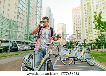 A cool adult man walks around the city on a rented bicycle, wears sunglasses and looks away against the backdrop of the cityscape. The tourist picked up a bicycle and posed for the camera