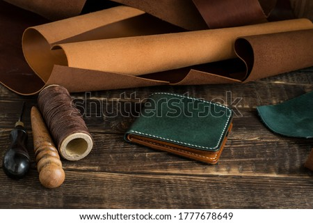 Leather craft or leather work. On work table of leathersmith there are pieces of leather, tool, waxed thread and leather wallet. Royalty-Free Stock Photo #1777678649