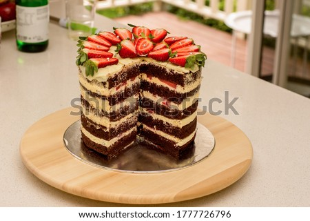 Delicious handmade double barrel tall layered cake decorated with strawberries on a cake stand Royalty-Free Stock Photo #1777726796