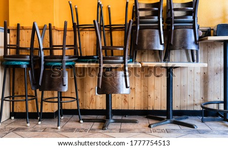 Chairs and Stools Stacked on Tables in an Empty Closed Restaurant during Covid-19 Pandemic #1777754513