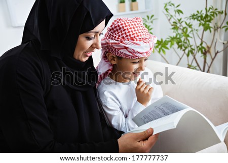 Happy Arabic mother and son together sitting on the couch and reading a book. #177777737