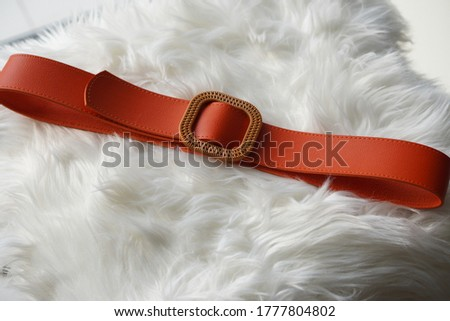 Woman belt with modern buckle upon a white hide blanket. Royalty-Free Stock Photo #1777804802