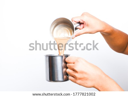 """A picture of men preparing """"teh tarik"""". Sweet milk tea been pull for mix well and create foam that is famous in Malaysia and South Asia region."""