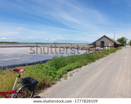 Wooden barn amidst vast area of sea salt flats in Samut Sakhon Thailand. There is a bicycle on the bottom left of the picture.