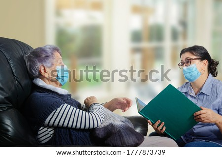 An everyday female caregiver reads books for an elderly woman. The corona-virus pandemic has made a difference. Both wearing face masks and keep their distance. Royalty-Free Stock Photo #1777873739