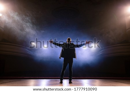 Showman. Middle Age Male entertainer, presenter or actor on stage. Arms to sides, smoke on background of spotlight. Rear view portrait of a male public speaker speaking at the microphone, pointing Royalty-Free Stock Photo #1777910090