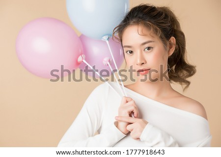 Young Asian girl holding balloons isolated image on light brown background