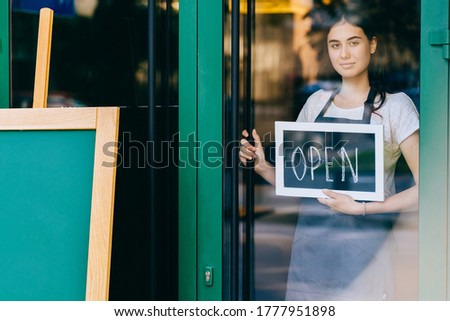 Young business woman hanging an open sign on a glass door. Coffee shop female owner showing chalkboard with open sign while opening store. Local business, hospitality, open after lockdown concept.