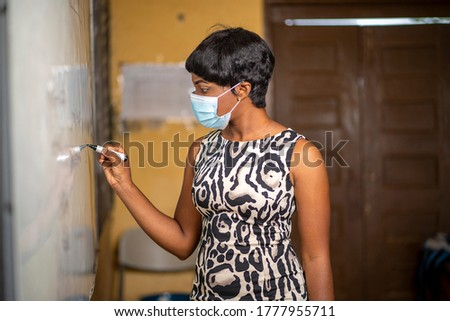 image of class teacher writing on marker board-black lady tutor in face mask after lock down-beautiful African madam with short hair in lecture room  #1777955711