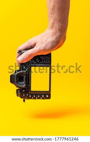 Modern SLR and mirrorless camera in male hands on yellow background flat lay copy space. Digital photography, body without lens, photographer's technique, digital camera, professional photo camera