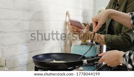 two unrecognized asian woman friends in kitchen cooking together. Women takes picture with cellphone while roommate frying pancake on pan on stove. lady record prepare dessert process on smartphone