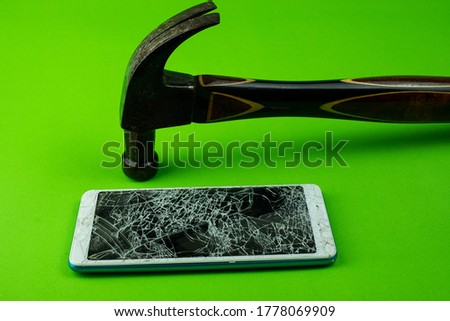 Hammering the phone smartphone screen is cracked on green background