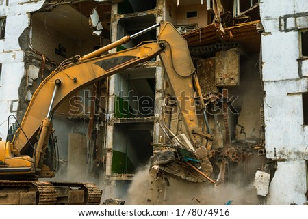 Demolition of a five-story apartment building recognized as emergency housing, close-up of an excavator bucket collects construction waste Royalty-Free Stock Photo #1778074916