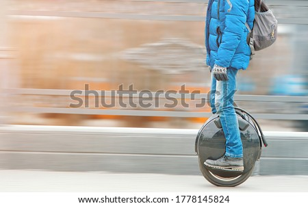 Man riding fast on electric unicycle on city street. Mobile portable individual transportation vehicle. Personal vehicle for transportation. Man with backpack on electric mono-wheel riding fast (EUC) #1778145824