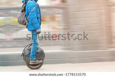 Young Man riding fast on electric unicycle on city street. Mobile portable individual transportation vehicle. Personal vehicle for transportation. Man with backpack on electric mono-wheel (EUC) #1778153570