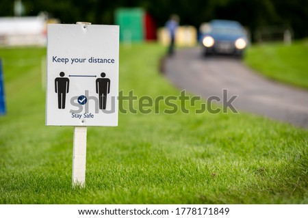 A Covid-19 social distancing sign staked into grass next to a road at an outdoor event.