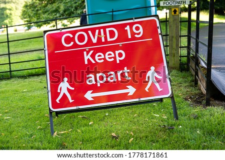 A Covid-19 social distancing warning sign at an outdoor event.
