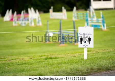 A Covid-19 social distancing sign staked into grass with an equestrian show jumping outdoor event in the background.