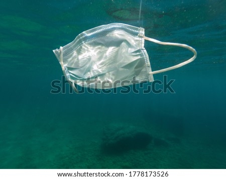 Used face mask floating in the sea, mediterranean sea. Catalonia, Spain. Covid-19 pollution. Coronavirus prevention risks #1778173526
