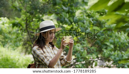 Woman go hiking and take photo on cellphone