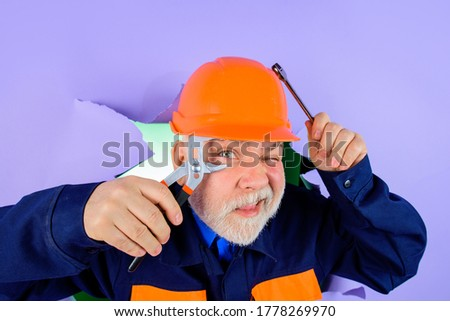 Repairment tools. Professional plumber holds pliers and wrench. Auto mechanic holds combination pliers. Builder with adjustable pliers looking through paper. Worker or builder in helmet with pliers. #1778269970
