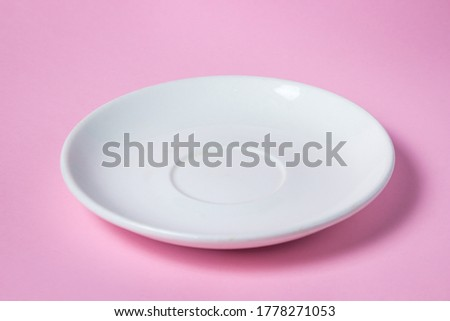 White saucer on a pink background. Empty white porcelain saucer stands on a pink surface #1778271053