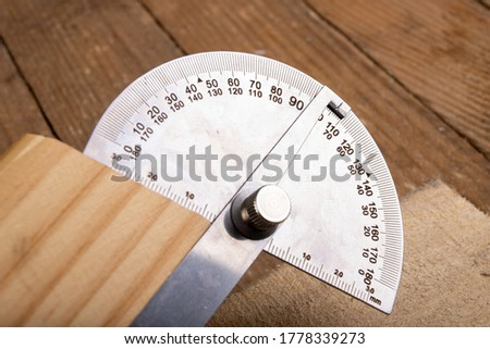Metal protractor for measuring in carpentry. Minor work in a home workshop. Place of work back.