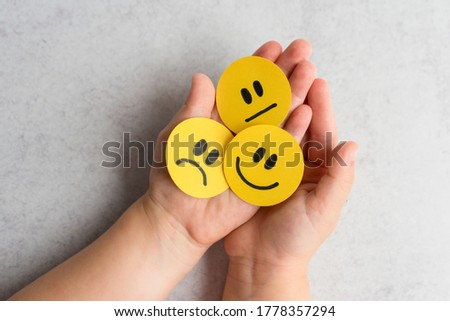 Kids emotions. Kids Hands with yellow smiley, sad and unsatisfied paper faces. Emotional intelligence concept.  Royalty-Free Stock Photo #1778357294