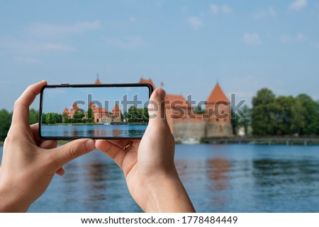 Tourist taking photo of Trakai Island Castle near Vilnius, Lithuania. Man holding phone and taking picture of medieval Gothic Island castle