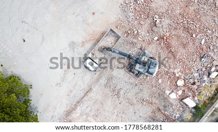 Aerial view of excavator demolishes an old building in city center. Destroyed concrete is loaded on the truck Royalty-Free Stock Photo #1778568281