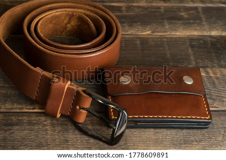 Handmade leather wallet and belt in cognac brown color on a wooden table. Vintage leather wallet and belt. Handmade leather goods. Leather craft. Royalty-Free Stock Photo #1778609891