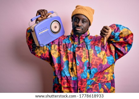 Young african american man listening to music holding portable vintage retro radio with angry face, negative sign showing dislike with thumbs down, rejection concept