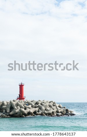 Red lighthouse above the breakwater Royalty-Free Stock Photo #1778643137