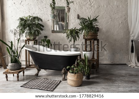Bathroom in vintage style with elegant interior, contemporary black tub, textile carpet, green plants in flower pots, mirror and copy space on white wall #1778829416