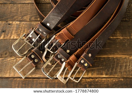 Lots of handmade men's leather belts on a wooden background. Classic men's leather belts in brown and cognac color. Handmade leather belts. Leather craft Royalty-Free Stock Photo #1778874800
