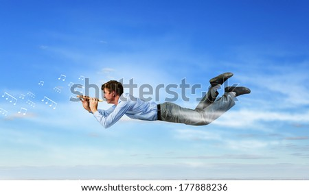 Young businessman flying in sky and playing fife #177888236