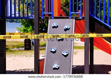 Children playground closed due to coronavirus pandemic lockdown. Yellow caution tape restricting the slide and climbing equipment. Royalty-Free Stock Photo #1778936888