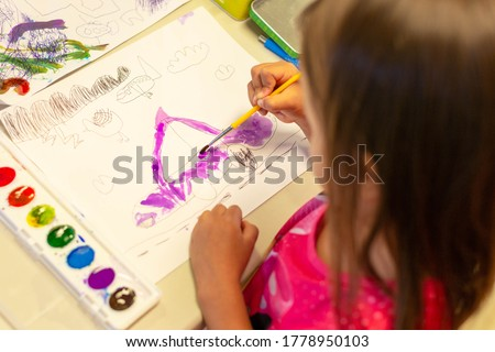 Little kid drawing and painting a picture. Children's art and creativity.