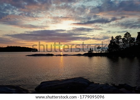 The sun goes over the horizon, a beautiful sunset over the lake, clouds in the blue sky. Horizontal photo of calm nature